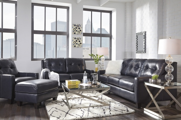 executive living room featuring black leather sofas and chairs with metal glass top tables and white patterned rug