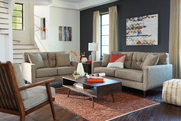 sterling plus living room featuring matching beige sofas with pillows with low wooden table over a red area rug
