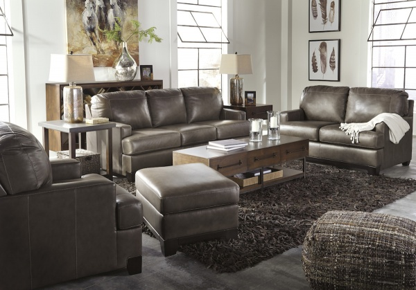 executive living room featuring brown leather sofas and chairs with brown furniture and accents