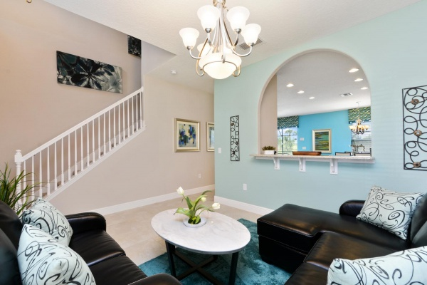 Eaglebay living room with black leather wraparound couch overlooking staircase and a blue wall