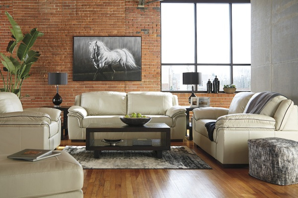 executive living room featuring cream leather sofas and chairs with brown wood table and painting of a horse