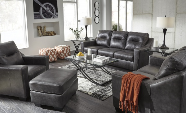 executive living room featuring grey leather sofa and chairs with black metal glass top tables and rust accents