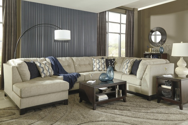 executive living room featuring cream wraparound sofa with brown wooden furniture and beige area rug