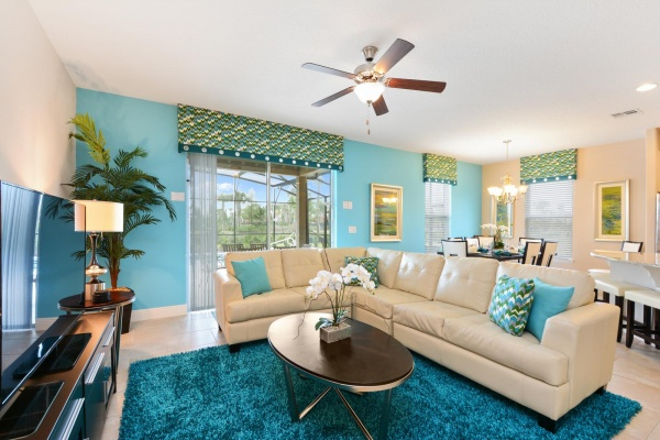 Eaglebay living room with cream leather wraparound couch with blue pillows and area rug with oval center table