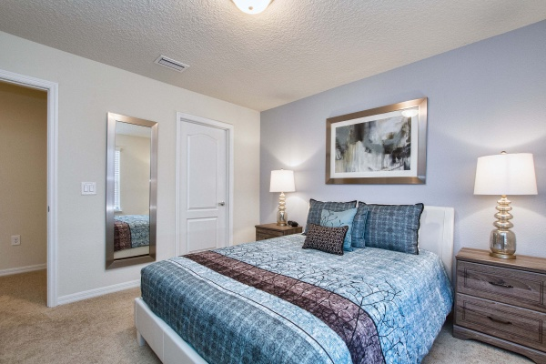 Hideaway bedroom with white bed with blue bedding with a light brown wooden bedroom set