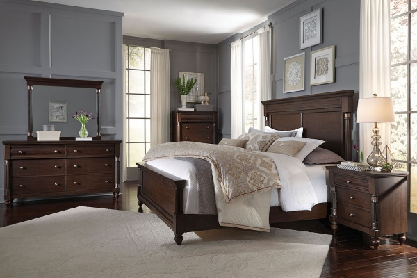 executive master suite featuring dark brown wooden bedroom set with white and beige accents and bedding
