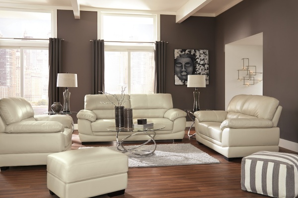 executive living room featuring cream leather sofas and chairs with metal round table and white area rug