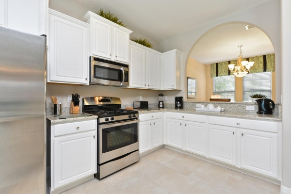 Eaglebay kitchen with white wooden cabinets, silver and black oven and marble countertops