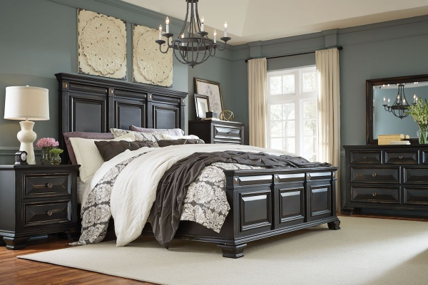 executive master suite featuring black wooden bedroom set with black and white accents and bedding