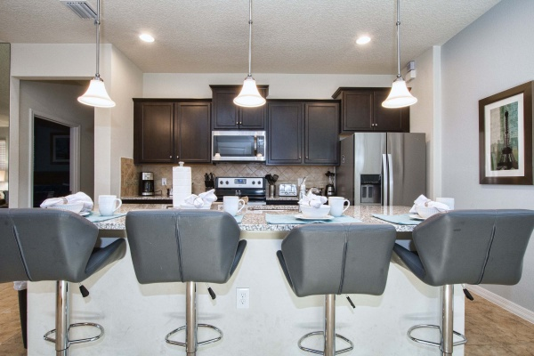 Hideaway kitchen and bar area with black leather bar stools. Kitchen has marble counter tops, and silver oven and fridge