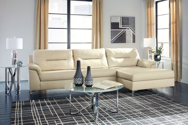 sterling plus living room featuring cream leather sofa with round glass top table with a black and white plaid rug