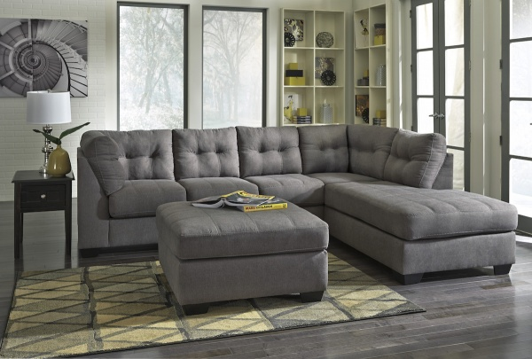sterling plus living room featuring with grey wraparound sofa and ottoman table with grey and yellow area rug