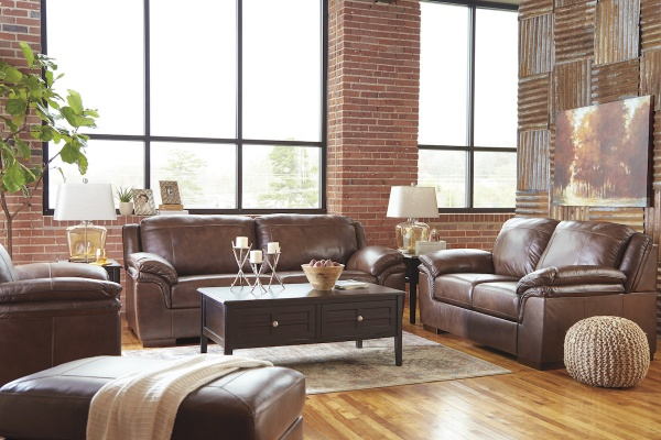 executive living room featuring  brown leather sofas and chairs with brown wooden furniture and hardwood floors