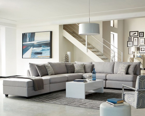 executive living room featuring grey wraparound sofa with grey accent pillows and a white rectangular shaped table