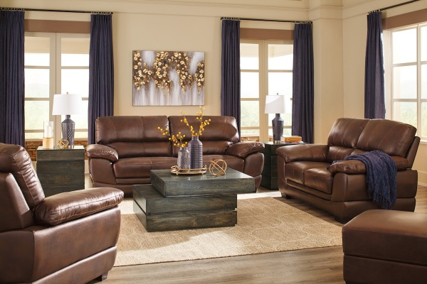 executive living room featuring brown leather sofas and chairs with wooden center table and cream area rug